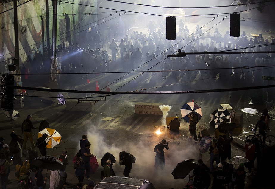 caption: Seattle police officers deployed tear gas, pepper spray, and flash-bang grenades on protesters shortly after midnight on Sunday June 7, 2020, in Capitol Hill. The next day, after a week of tense, nightly standoffs between demonstrators and a fortified line of police in riot gear, the police line moved out and the precinct windows were boarded up. Over the PA system, protest organizers called for a peaceful gathering and reiterated the overall goal: to defund the Seattle Police Department.