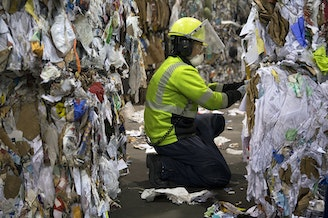 Recology employee Zakarya Sales works at the final quality control station, removing any visibly obvious contaminants from sorted bales, at the Recology Materials Recovery Facility on Tuesday, October 31, 2017, on S. Idaho St., in Seattle.