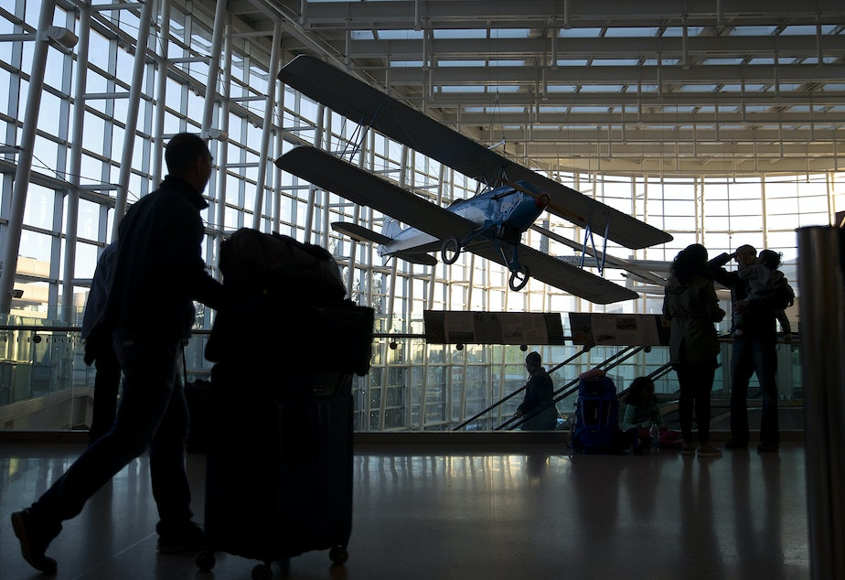 caption: Passengers walk through the arrivals terminal on Monday, December 11, 2017, at Seattle-Tacoma International Airport.