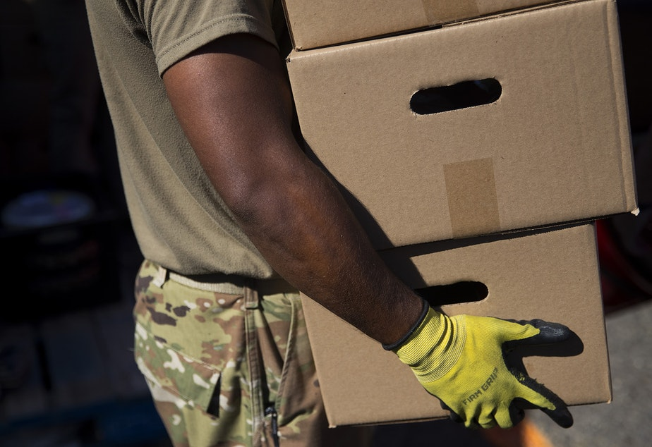 caption: Spc. Andre Bhatt with the Washington National Guard loads boxes of food into the back of a vehicle on Tuesday, September 22, 2020, at the Tukwila Pantry Food Bank on South 140th Street in Tukwila.