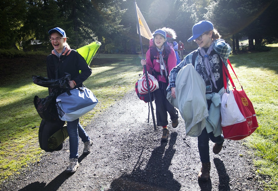 From left, Zephyra Bingham, 14, Ariana Spradlin, 13, and Rachel Becking, 13, carry their belongings before setting up their tents during the Boy Scouts of America Bootcamp for girls on Saturday, October 6, 2018, at Camp Thunderbird in Olympia.