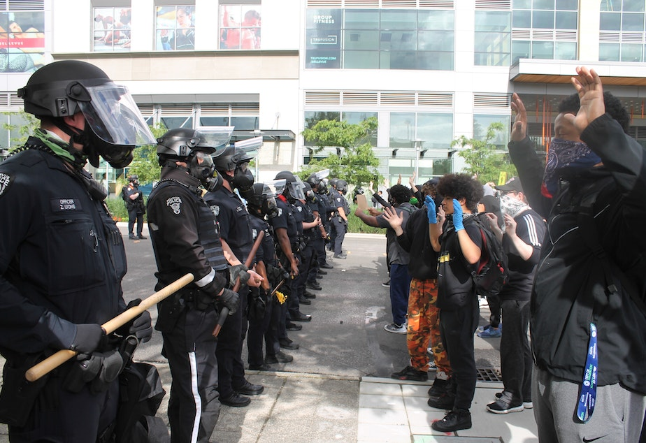 caption: Protesters face Bellevue Police  in downtown Bellevue Sunday, May 31, 2020. The crowd was protesting the death of an unarmed Black man, George Floyd, killed by police officers in Minneapolis.
