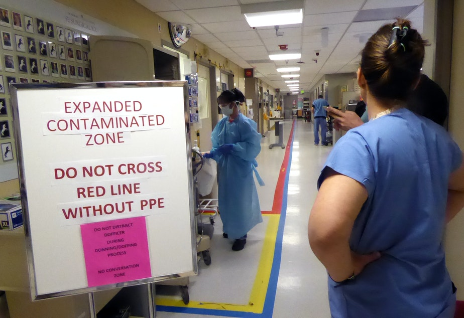 caption: A view of the entrance of the Covid ICU at University of Washington Medical Center on April 24, 2020. Amy Haverland, the nurse manager, is on the right. The taped red line down the middle of the aisle indicates where only medical staff with protective gear may go.