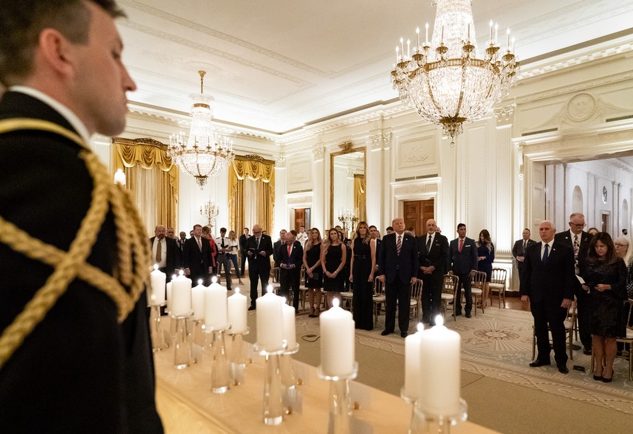 "caption: President Donald Trump and First Lady Melania Trump join guests in singing ""America the Beautiful"" during a reception in honor of Gold Star Families on Sept. 27, in the East Room of the White House. On Thursday, Trump suggested he may have contracted COVID-19 from one of the family members at the event."