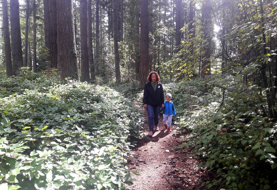 Lori Sechrist of Save the Weyerhaeuser Campus walks a trail on the old campus with her grandson