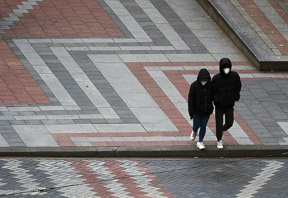 caption: Two people wearing masks cross 4th Avenue while walking along Pine Street on Tuesday, March 24, 2020, in Seattle.
