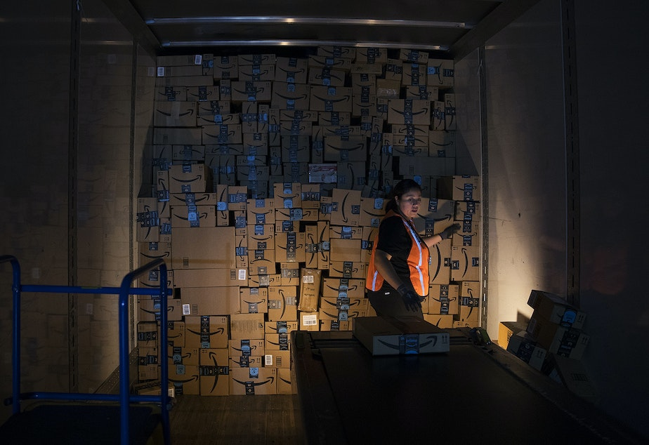 caption: Amazon employee Andrea Neri stacks boxes in the back of a delivery truck on the ship dock at an Amazon fulfillment center on Friday, November 3, 2017, in Kent.