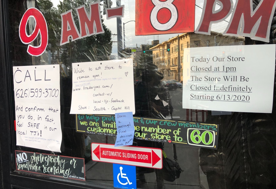 caption: The front doors of the Trader Joe's at 1700 E. Madison St. on June 14th. Signs announcing the indefinite closure were joined by newer ones advocating to reopen the store.