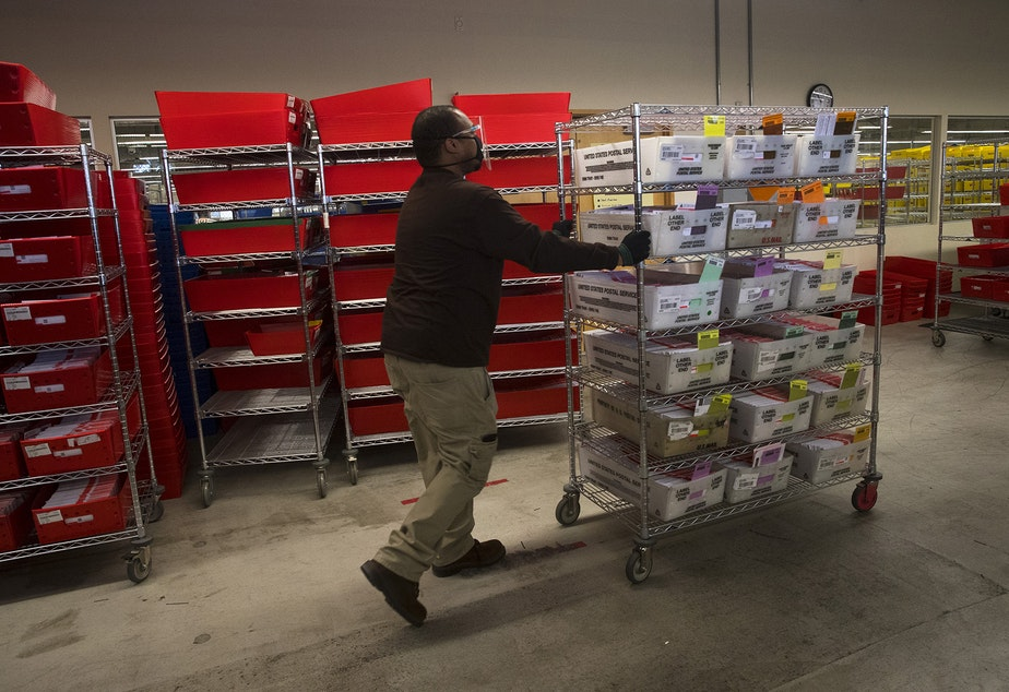 caption: An election worker moves a rack full of sorted ballots on Wednesday, October 28, 2020, at King County Elections in Renton.