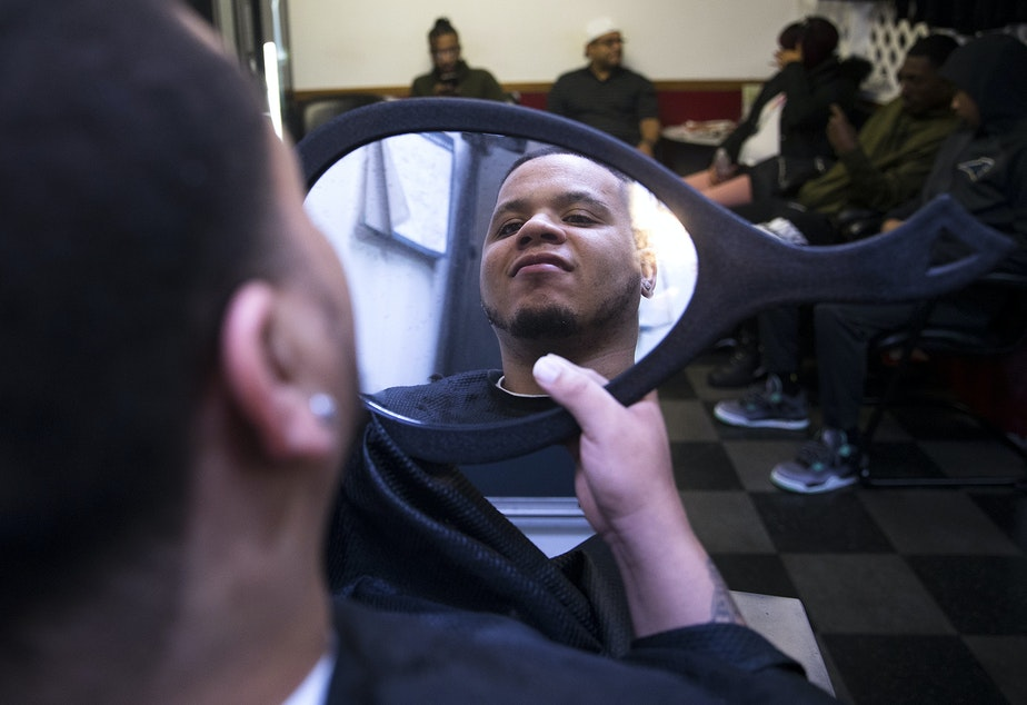 caption: DaShawn Horne looks into a mirror after having his hair cut at Salon Edwards on Monday, December 31, 2018, in Federal Way.
