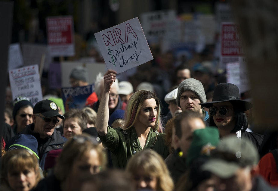 """Jesse Pettibone, 23, center, marches on Saturday, March 24, 2018, during March For Our Lives in Seattle. """"Youth, queer people and people of color are often the victims of gun violence and we need to disarm that hate now,"""" Pettibone said."""