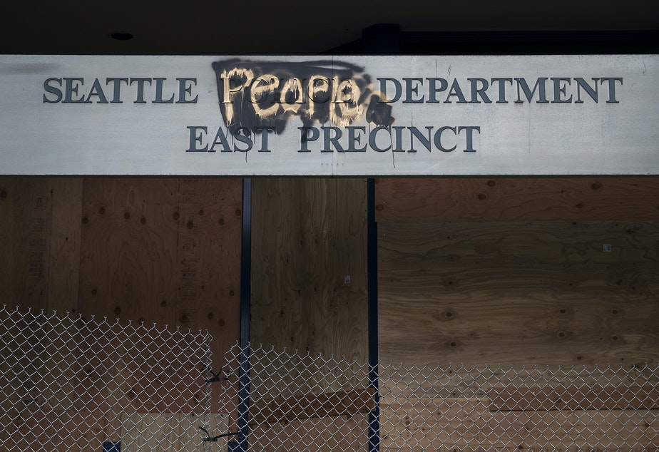 caption: The boarded up Seattle Police Department's East Precinct building is shown on Tuesday, June 9, 2020, near the intersection of 12th Avenue and East Pine Street in Seattle.