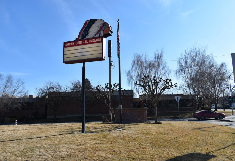 """A brick school building is silhouetted against a blue sky, with bare trees lining the street in front of it while a school billboard stands in the middle of a lawn. The sign has a Native American mascot illustrated above the words """"North Central Indians."""""""