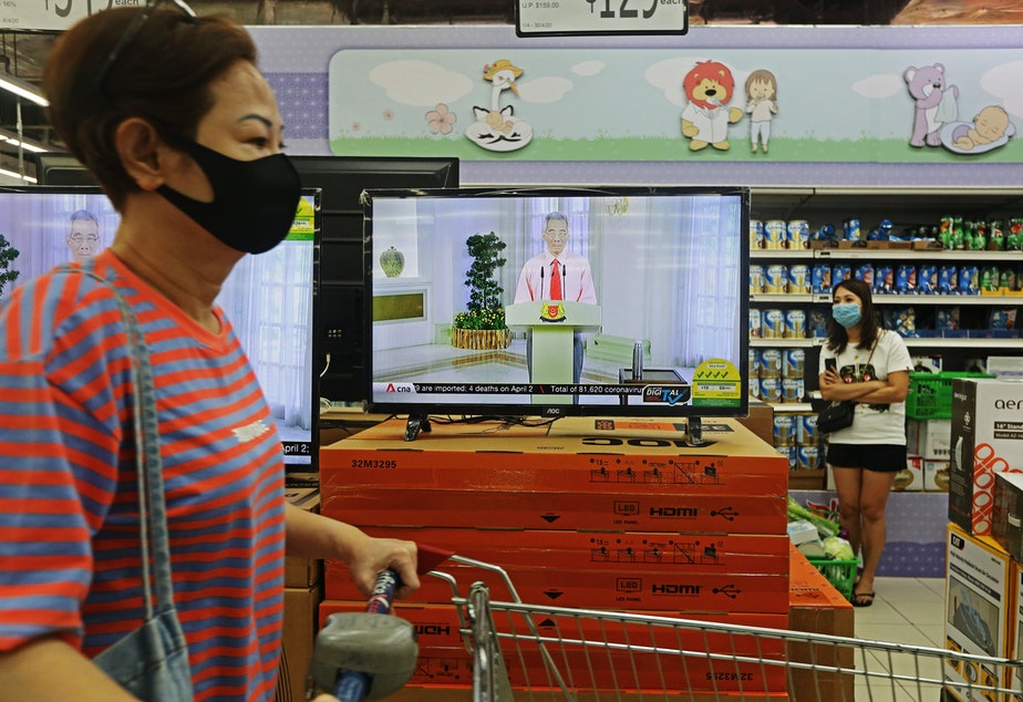 caption: Singapore Prime Minister Lee Hsien Loong addresses the country via live telecast while customers shop for groceries on April 3. Early in the outbreak, Singapore did not recommend masks for the public because of shortages, but began urging public mask-wearing this month to prevent transmission by infected people who were not showing symptoms.