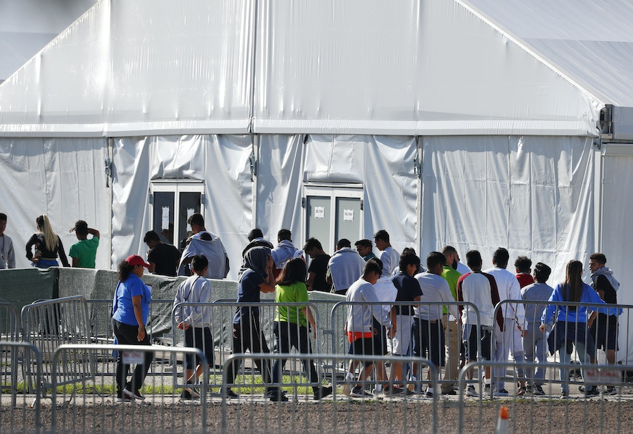 caption: Children line up in February 2018 to enter a tent at the Homestead Temporary Shelter for Unaccompanied Children in Homestead, Fla. Many of these kids were taken from their parents after crossing the border illegally.