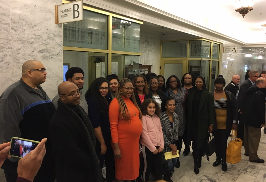 caption: Suppporters of a bill to ban race-based hair discrimination pose for a photo following a public hearing in Olympia on Tuesday.