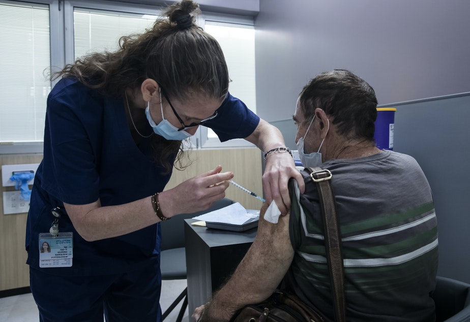 caption: A man receives the Pfizer COVID vaccine in Ramat Gan, Israel. A small Israeli study suggests vaccinated people who experience rare breakthrough infections may develop symptoms that last as long as six weeks.