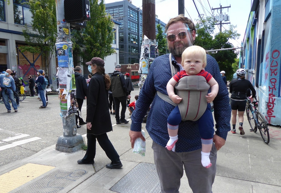 caption: Gabe Magic, and his 8-month-old Tilden, at the Capitol Hill Autonomous Zone, or CHAZ, in Seattle on June 11, 2020. Magic got his face shield from the Post Office; it was Tilden's first time in the area. They live about eight blocks away.