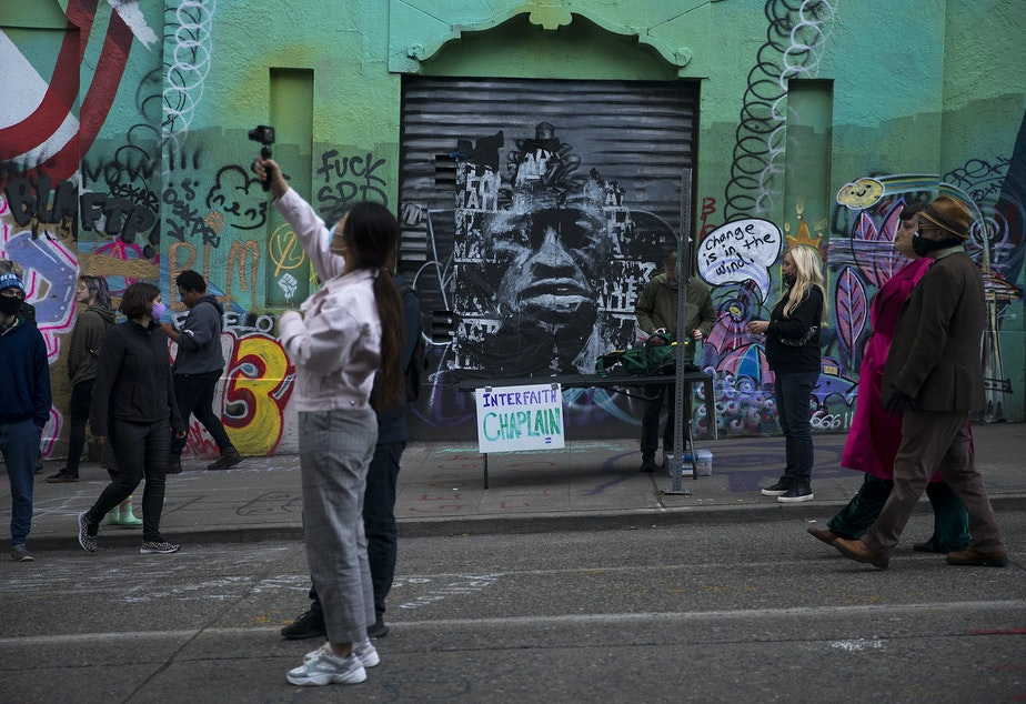 caption: A mural of George Floyd is displayed behind the Interfaith Chaplain station at the Capitol Hill Autonomous Zone, CHAZ, or Capitol Hill Occupied Protest, CHOP, on Saturday, June 13, 2020, in Seattle.