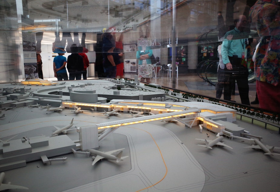 caption: Sea-Tac visitors pass a model of the International Arrivals Terminal, to be completed in 2019.