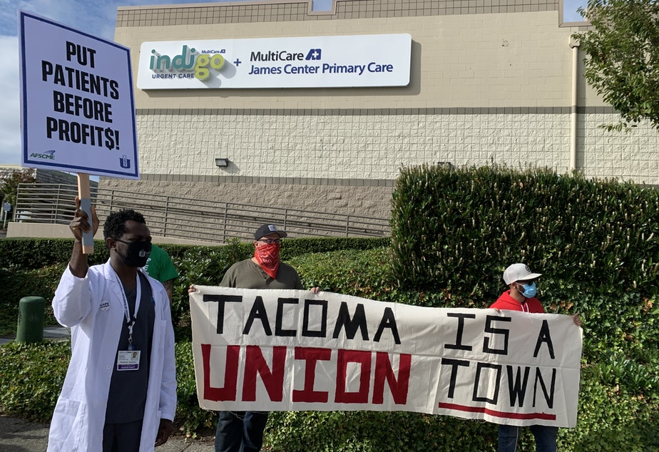 caption: Physician assistant Frantz Alphonse demonstrates in front of a Tacoma MultiCare Indigo Urgent Care clinic location with local members of the International Longshore and Warehouse Union.
