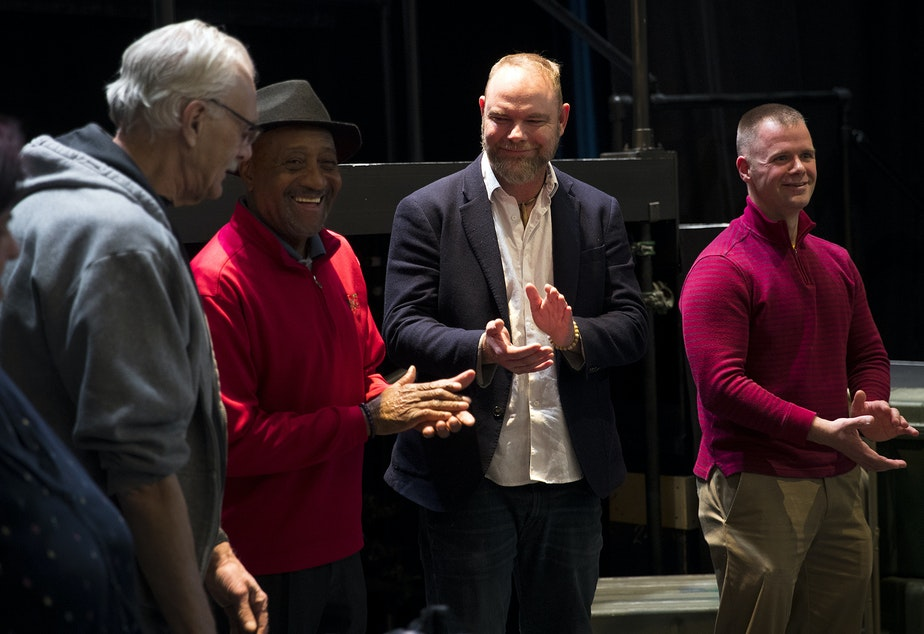 caption: From left, veterans Michael Hammond, Mertiss Thompson, Ryan Mielcarek, and Peter Michaud clap after their final rehearsal presentation on Thursday, October 31, 2019, at Seattle Opera on Mercer Street in Seattle.