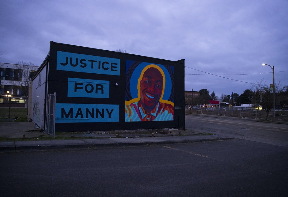 """caption: A mural honoring 33-year-old Manuel Ellis is shown as the sun goes down on Sunday, February 28, 2021, near the intersection of Martin Luther King Jr. Way and South 11th Street following a silent march honoring him in Tacoma. """"We want to make sure that Bob Ferguson knows that Tacoma does not forget trespasses against us,"""" said Jamika Scott, with the Tacoma Action Collective, to the crowd at People's Park.""""We won't forget Manny Ellis,"""" said Scott."""