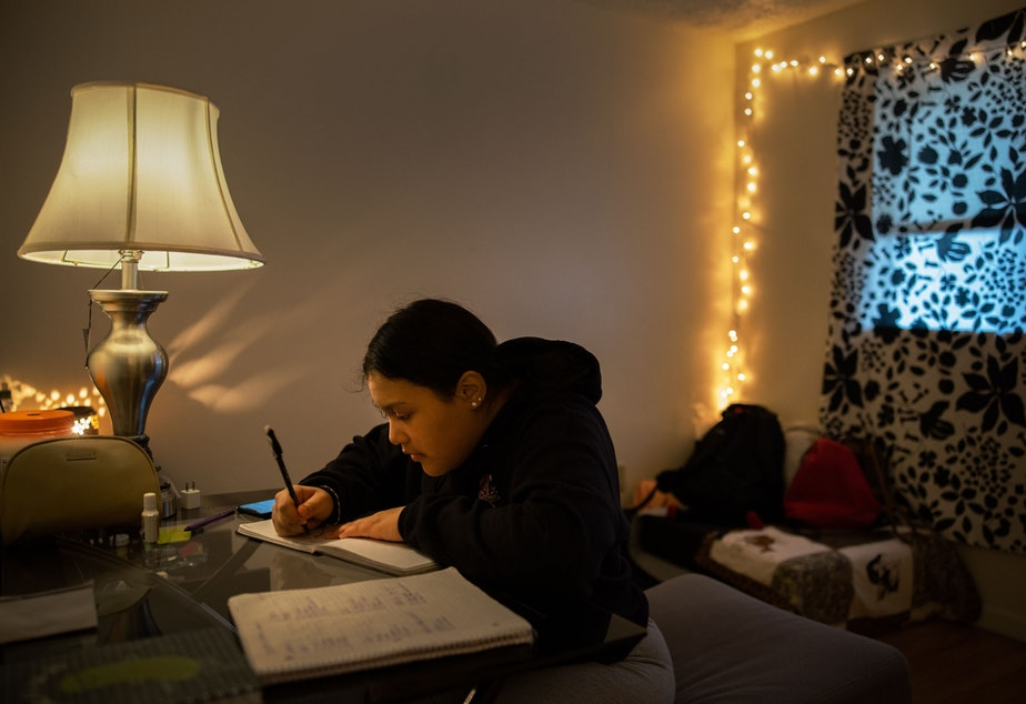 caption: Michelle Aguilar Ramirez works on her daily journaling which she uses to help her reflect and process her life, in her room in Spokane, Washington.