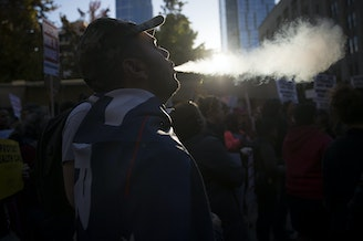Armen, a member of the UW College Republicans blows smoke into the air during the 'Cancel Kavanaugh - We Believe Survivors' march and rally on Thursday, October 4, 2018, at Westlake Park in Seattle.