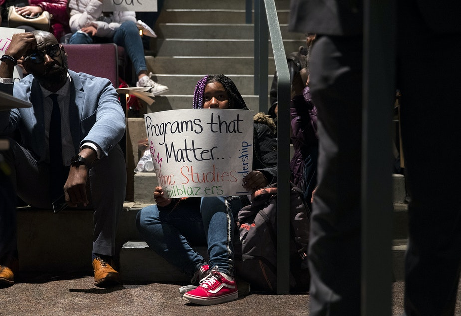 caption: Sharae Miller, a 9th-grade student at Garfield high school holds a sign showing support for ethnic studies programs at a public meeting to address concerns about abusive teachers on Thursday, February 13, 2020, at the Quincy Jones Performing Arts Center at Garfield High School in Seattle.