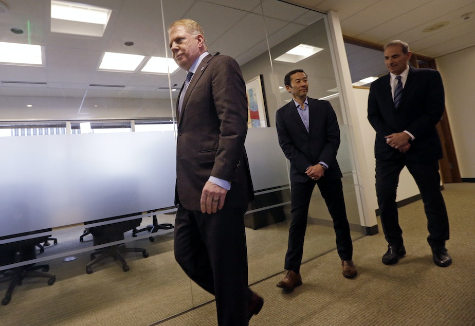 caption: Seattle Mayor Ed Murray, left, walks past his husband, Michael Shiosaki, center, and his attorney, Bob Sulkin, to make a statement to media members Friday, April 7, 2017, in Seattle.