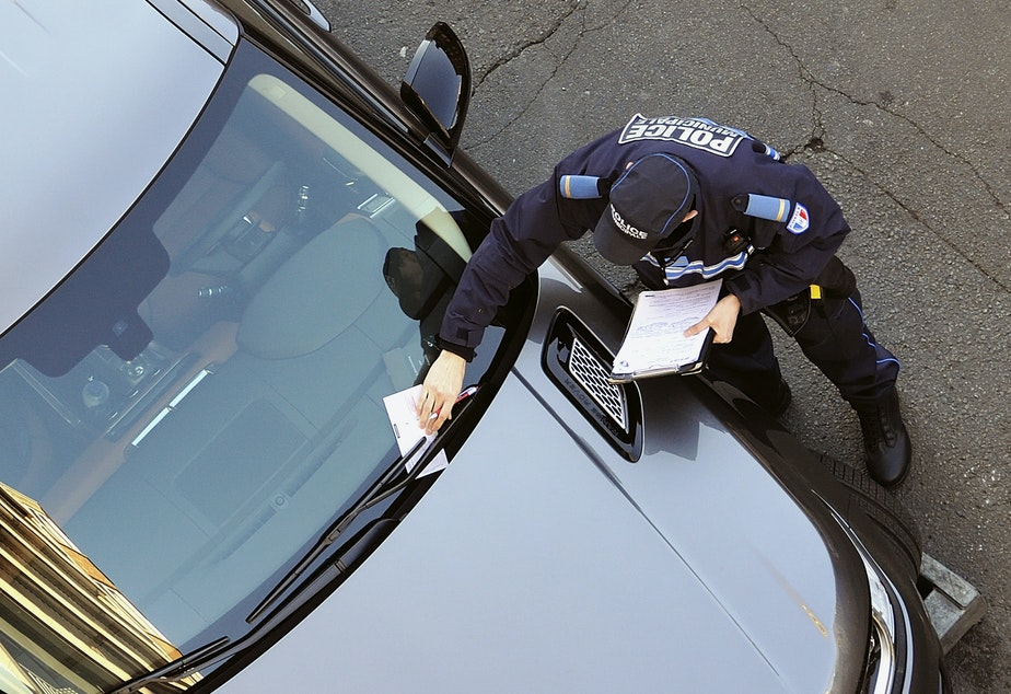 caption: A policeman issues a parking ticket in this 2013 photo. A federal appeals court held Monday that using chalk to mark tires for purposes of parking enforcement violates the U.S. Constitution.
