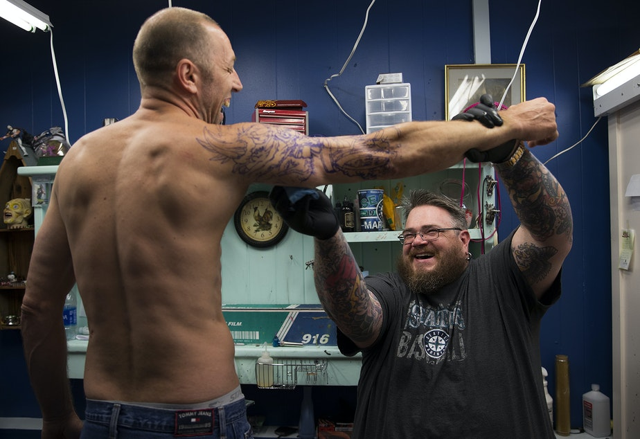 Mike Heath, left, laughs  as Blue Collar Tattoo owner Sean Ewan cleans his arm before tattooing a tribute to Metallica, on Wednesday, July 5, 2017, in Bremerton, Washington. Tap or click on this image for the slideshow.