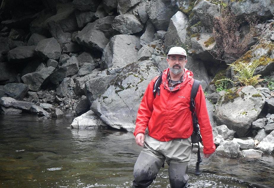 Biologist Jon-Paul Shannahan standing in front of habitat-smothering riprap along Grandy Creek in the Skagit basin.