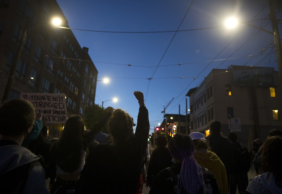 caption: Protesters make their way back to the Capitol Hill Occupied Protest zone after marching to the Seattle Police Department's West Precinct building on the 19th day of protests in Seattle following the violent police killing of George Floyd, on Tuesday, June 16, 2020.