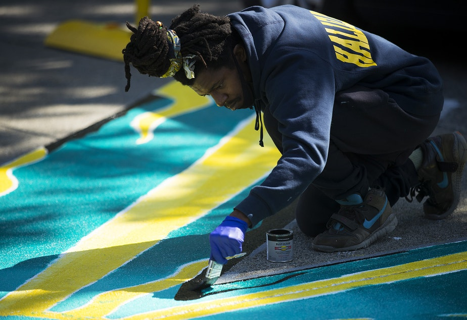 caption: Local artist Ari paints the letter K in the Black Lives Matter street mural on Friday, October 2, 2020, on E. Pine Street in Seattle.