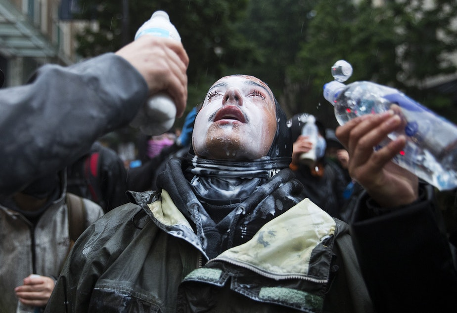 caption: A protester has milk and water poured on their face after they were sprayed with tear gas on Saturday, May 30, 2020, near the intersection of 5th and Pine Streets in downtown Seattle. Thousands gathered for a demonstration following the violent police killing of George Floyd, a Black man who was killed by a white police officer who held his knee on Floyd's neck for 8 minutes and 46 seconds, as he repeatedly said, 'I can't breathe,' in Minneapolis on Memorial Day.