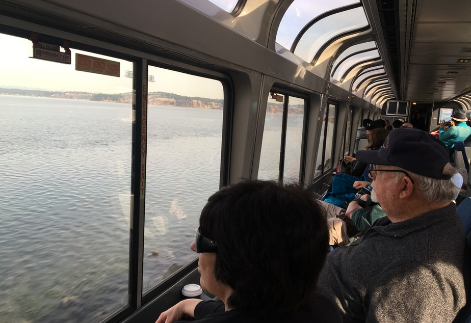 caption: Passengers on Amtrak's Coast Starlight watch Puget Sound roll by