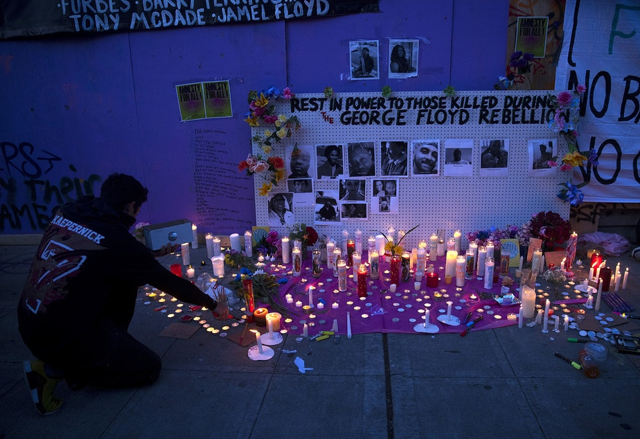 "caption: ""Rest in power to those killed during the George Floyd Rebellion"" reads the wall above a candlelight vigil honoring those killed unjustly at the hands of law enforcement on Tuesday, June 2, 2020, at the intersection of 11th Avenue and East Pine Street in Seattle."