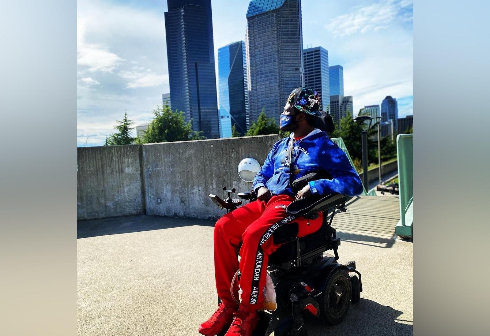 A man in a wheelchair overlooks a city skyline.