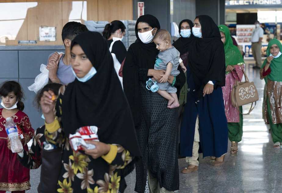caption: Families evacuated from Kabul, Afghanistan, walk through the terminal before boarding a bus after they arrived at Washington Dulles International Airport, in Chantilly, Va., on Tuesday, Aug. 24, 2021.