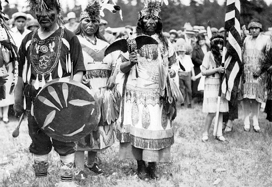 caption: Woman holding spirit dance rattle and man holding drum at traditional Lummi Native American dance, Bellingham, Washington, ca. 1930-1933