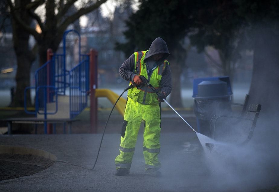 caption: Khai Tran, a utility worker with Seattle Parks and Recreation, sprays water onto a swing-set before a mixture of bleach and water is applied to the West Woodland Park Playground as a result of the coronavirus outbreak on Thursday, March 19, 2020, in Seattle. KUOW Photo/Megan Farmer
