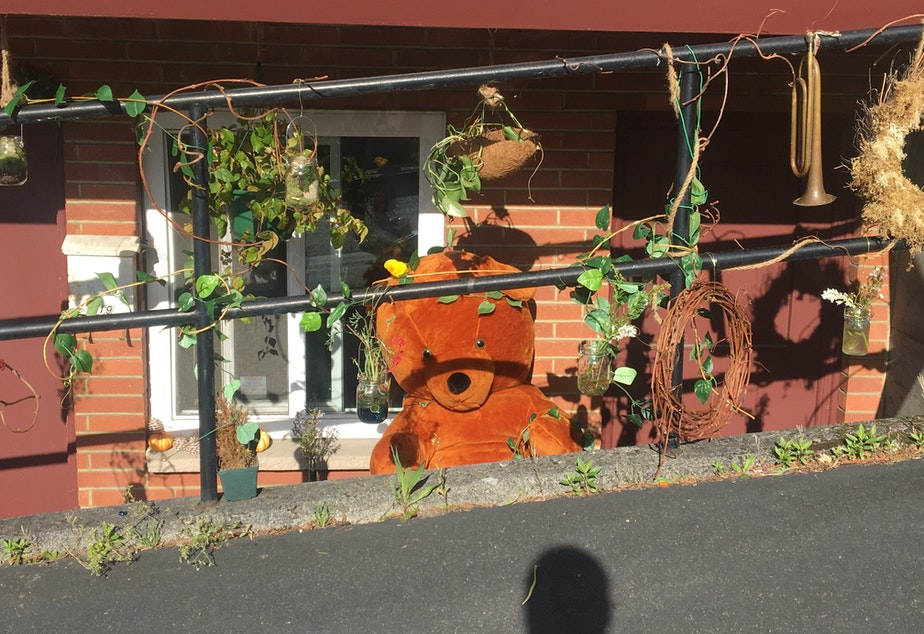 caption: Mark Siano's teddy bear decorates the front porch of his home, ready for #artdisplays4homestays