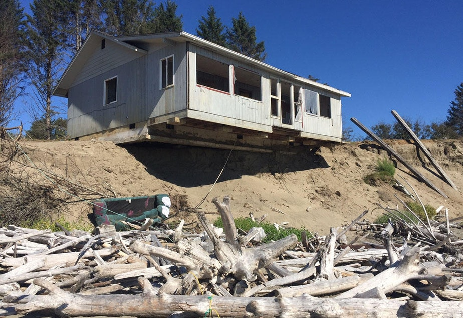 caption: Coastal erosion is washing away beachfront communities in Washington state. In 2018, reporter Tom Banse predicted this home at Washaway Beach, Washington, would be the next in a long series of homes to fall into the sea.