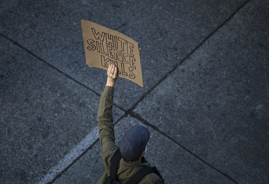 caption: FILE: An individual demonstrating for racial justice holds a sign that reads 'White Silence Kills,' on Sunday June 7, 2020, near Cal Anderson Park in Seattle.
