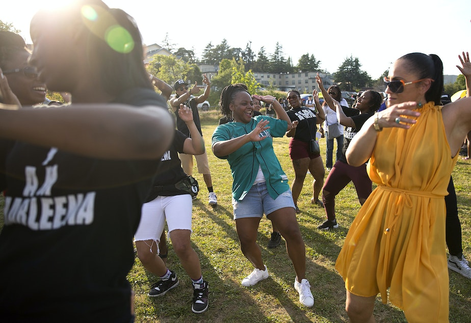 caption: Shakiah Danielson, center, dances with friends and family of Charleena Lyles during the one year remembrance, reflection and healing event on the anniversary of her death on Monday, June 18, 2018, at Magnuson Park in Seattle.