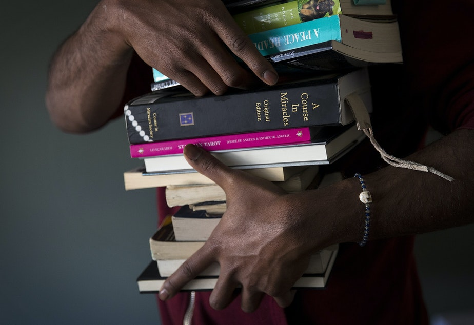 Jordan packs his belongings, including a stack of books, at his studio apartment on Tuesday, February 26, 2019, after receiving an eviction notice, on 4th Avenue South in Seattle.
