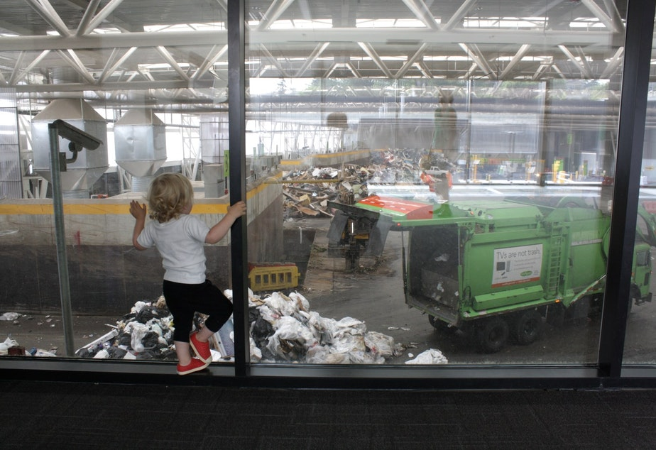 caption: A toddler watches the garbage trucks at Wallingford's rebuilt transfer station