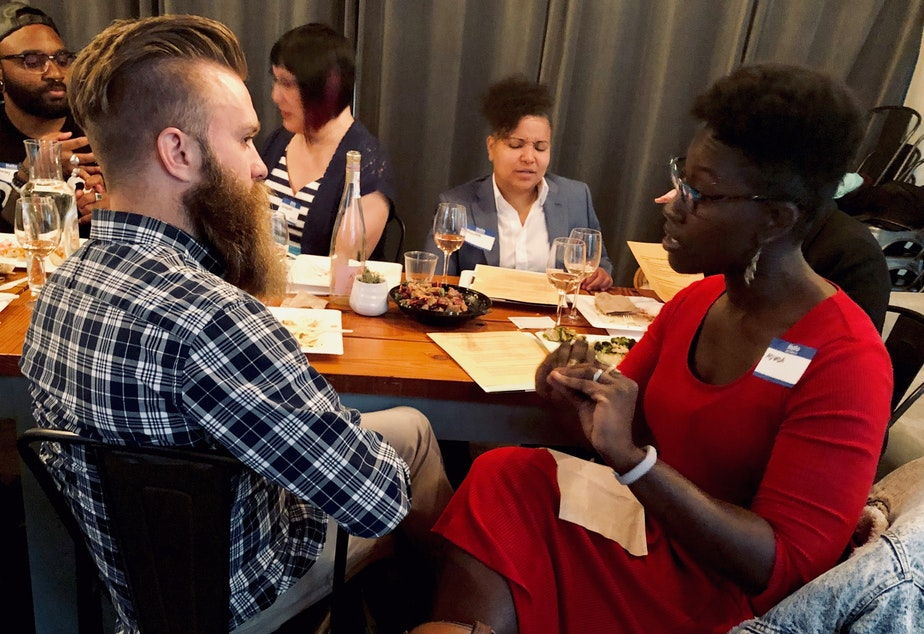 caption: Curiosity Club member Jeffrey Howard talks with KUOW producer Adwoa Gyimah-Brempong at The Cloud Room in Seattle for Queeriosity Club. Fellow Club members Timothy Bardlavens (far left), Ginger Chien (center) and Mellina White Cusack (right) chat in the background. June 6, 2019.